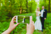 Somebody is using smartphone to make a photo of newlyweds in summer forest